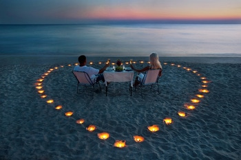 Couple having dinner on the beach with candles arranged in a heart