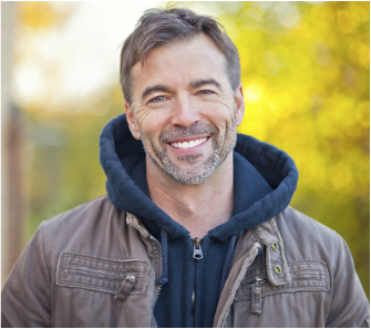 Caucasian man with short brown hair and salt and pepper facial hair smiling